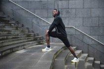 Giovane uomo esercitare, allungando le gambe sui gradini, all'aperto — Foto stock