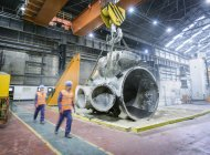 Steelworkers walking past large casting — Stock Photo