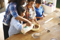Mother and children baking in kitchen at home — Stock Photo
