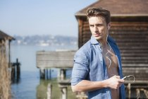 Mid adult man on pier, listening to music — Stock Photo