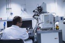Assistant de laboratoire travaillant au microscope électronique à balayage — Photo de stock