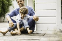 Mid adult man and son laughing and tickling feet on porch — Stock Photo