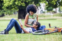 Boy and mother reading and relaxing in park — Stock Photo