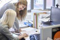 Dos empresarias revisando el papeleo en el escritorio de la oficina - foto de stock