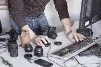 Мужчина фотограф, работающий с компьютером в студии — стоковое фото