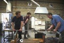 Мужской стеклодув в мастерской с помощью паяльной лампы — стоковое фото