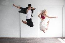 Dancers practicing jumping in empty studio — Stock Photo
