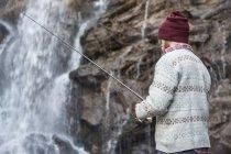 Homem pesca por cachoeira — Fotografia de Stock
