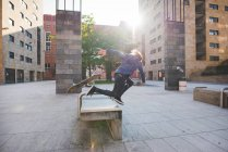 Young male skateboarder falling head first whilst skateboarding on urban concourse seat — Stock Photo