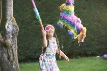 Mädchen spielt Pinata im Garten — Stockfoto