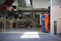 Mechaniker-Studenten lesen Anleitung in Reparaturwerkstatt — Stockfoto