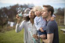 Mother blowing bubbles, father holding son — Stock Photo