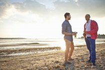 Men drinking beer and chatting on beach — Stock Photo