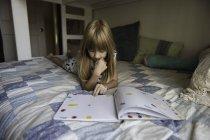 Giovane ragazza sdraiata sul letto lettura libro — Foto stock