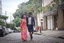 Coppia che cammina per strada acciottolata, sorridendo — Foto stock