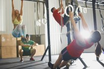 People working out with gymnastic rings in gym — Stock Photo