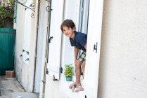 Retrato de menino olhando para fora de férias apartamento janela borda, França — Fotografia de Stock
