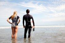 Coppia giovane affacciata sul mare, giovane che porta la tavola da surf — Foto stock