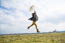 Adolescente en el campo con paraguas - foto de stock
