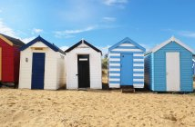 Row of beach huts on sand in bright sunlight — Stock Photo