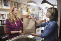 Shop assistant handing shopper shopping bag — Stock Photo