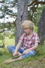 Мальчик чистит ветку дерева ножом — стоковое фото