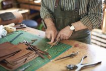 Male worker in leather workshop, checking sharpness of knife on leather, mid section — Stock Photo