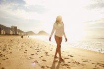 Mature woman strolling on sunlit Copacabana beach, Rio De Janeiro, Brazil — Stock Photo