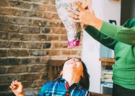 Mother and son playing with pinata at home — Stock Photo