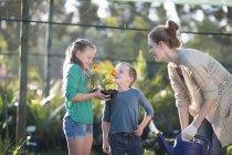 Брат и сестра с матерью пахнут растениями на участке — стоковое фото