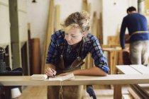 Young craftswoman making notes in pipe organ workshop — Stock Photo
