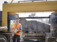 Портрет працівника кар'єру перед великим скелею, що розрізається у кам'яній пили — стокове фото