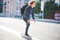 Молодые мужчины скейтбордист, скейтбординг вдоль тротуара — стоковое фото