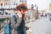 Giovane hipster maschio con i capelli rossi e la barba chatta su smartphone sulla strada della città — Foto stock