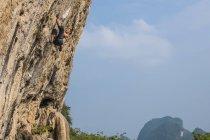 Faible angle vue du jeune grimpeur mâle escalade au Mont blanc - une falaise de calcaire de Yangshuo, Guangxi Zhuang, Chine — Photo de stock