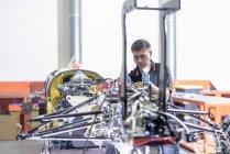 Инженер с автомобилем в стадии строительства на заводе гоночных автомобилей — стоковое фото