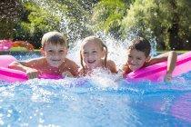 Portrait of three children splashing on inflatable mattress in garden swimming pool — Stock Photo