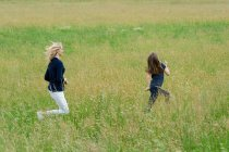 Mother and daughter running through long grass field — Stock Photo