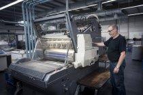 Worker operating print machine in printing workshop — Stock Photo
