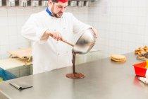 Gießen Schokolade auf der Theke in der Konditorei Koch — Stockfoto