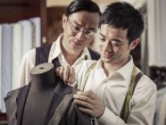 Father monitoring son in family tailoring business — Stock Photo