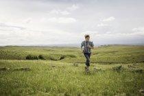 Teenage boy running in landscape, Cody, Wyoming, USA — Stock Photo