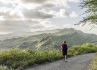 Jovem turista do sexo masculino fotografando com SLR digital no caminho da costa Makapuu, Oahu, Havaí, EUA — Fotografia de Stock