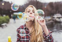 Portrait of young woman on waterfront blowing bubbles,  Lake Como, Italy — Stock Photo