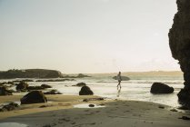 Reifer Mann zu Fuß in Richtung Meer, mit Surfbrett — Stockfoto