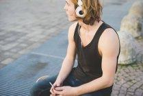 Young man sitting at sidewalk listening to headphone music — Stock Photo