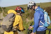 Велогонщики используют смартфон, прикрепленный к велосипеду — стоковое фото