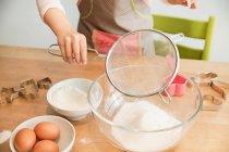 Girl sieving flour into mixing bowl — Stockfoto