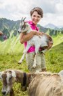 Young woman holding kid goat, Tyrol, Austria — Stock Photo