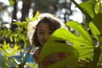Junges Mädchen lächelnd, stehend unter Laub — Stockfoto